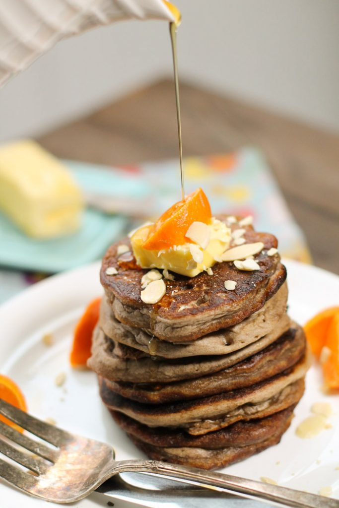 stack of dark brown pancakes topped with fresh butter and orange wedge and a drizzle of syrup atop a white plate