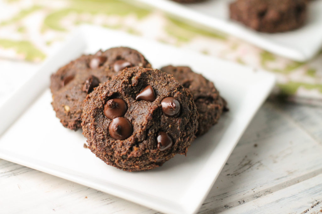 a white plate with three almond flour chocolate cookies.
