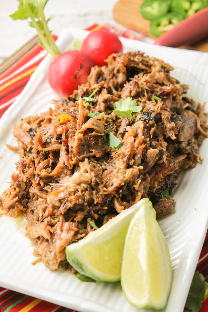 crispy carnitas atop a white plate with fresh lime wedges and whole red radishes
