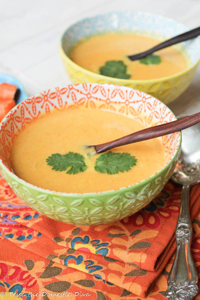 two festive bowls filled with a Thai inspired creamy carrot soup with cilantro, chilies, and olive wood spoons