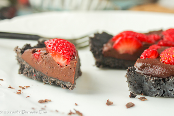 close up of a triangle bite of a no bake cookie crust with a chocolate layer and fresh strawberries pressed into the top