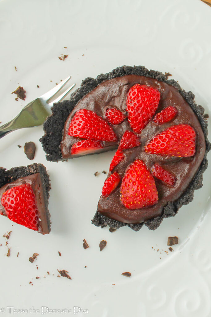 a fluted cookie crust tart with a chocolate ganache and halved fresh strawberries pressed into the top