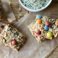 horizontal hemp granola bars with dye free m & m's from overhead on parchment