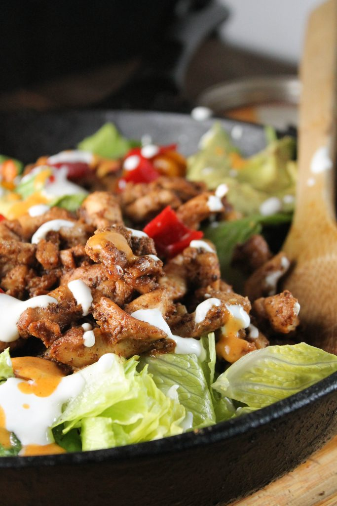 vertical image of well seasoned chicken fajitas topped with a drizzle of crema in a cast iron pan with wooden serving spoon