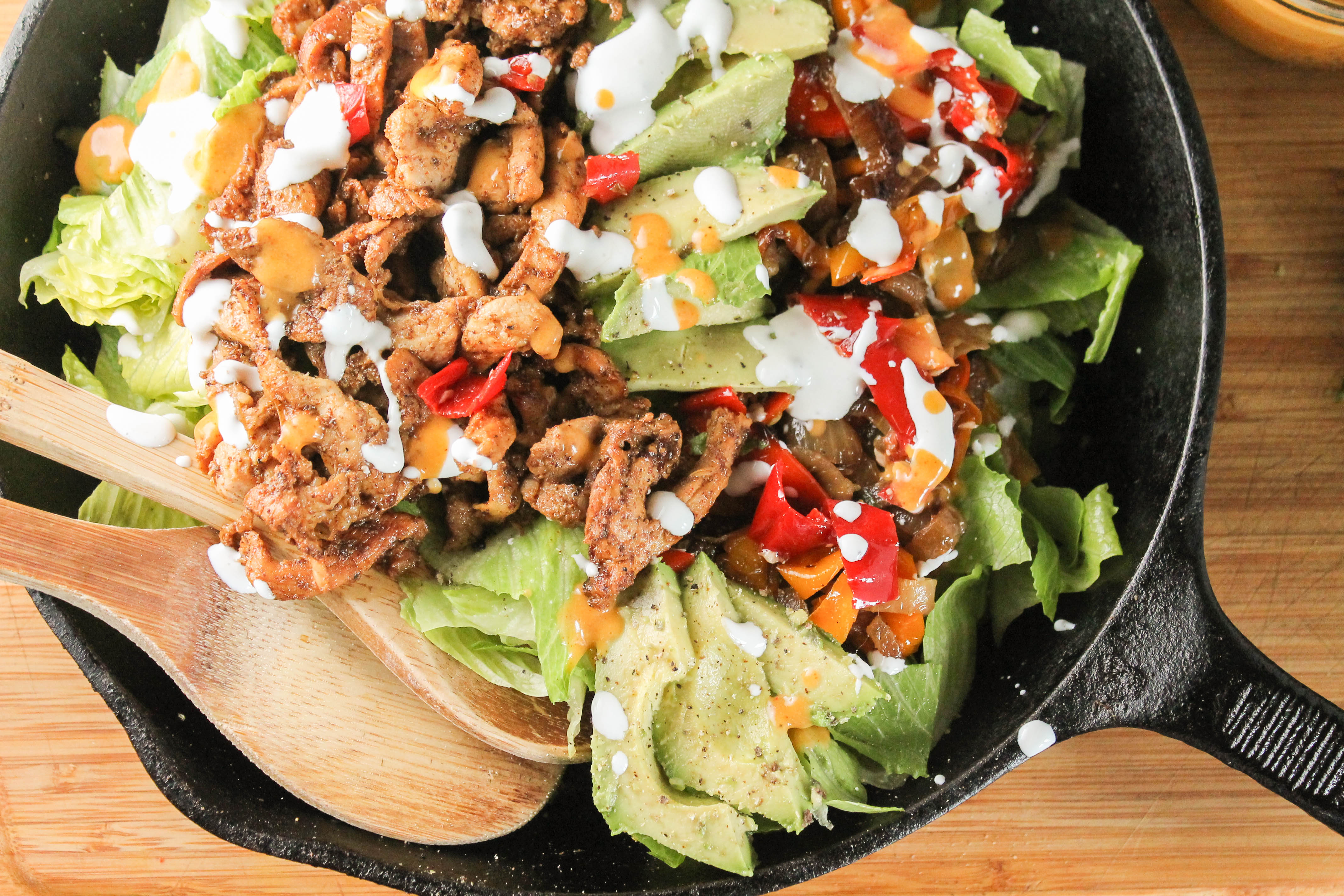 paleo chicken fajitas with charred onions and peppers topped with a dairy free creamy drizzle in a cast iron pan with wooden serving spoons