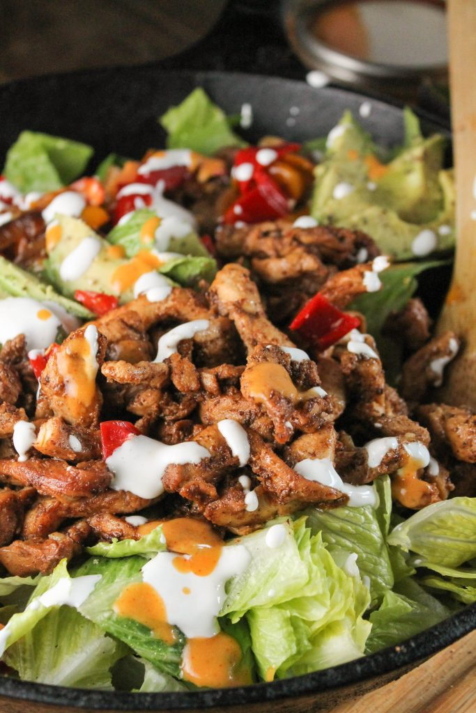 a front view close up of a cast iron skillet with fresh chicken fajitas topped with sour cream atop a bed of fresh romaine