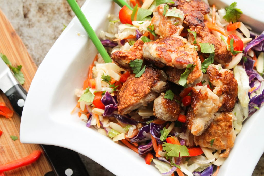 Paleo Sesame Chicken served on chopped carrots and cabbage in a white bowl