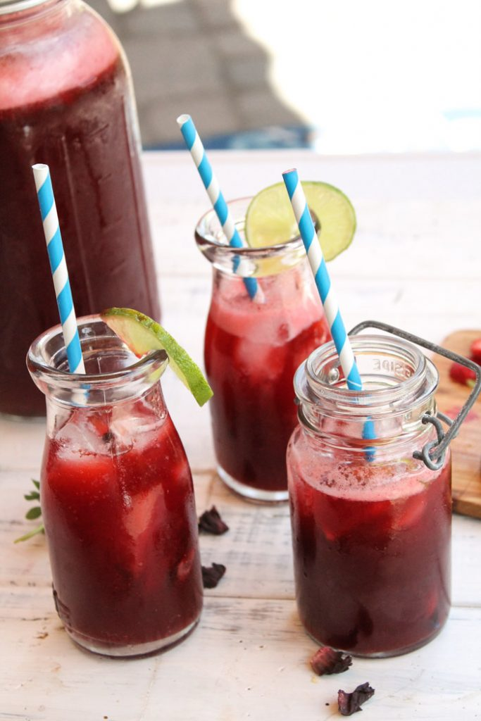 3 glasses of deep red hibiscus lime strawberry tea on a white board with large mason jar pitcher in background