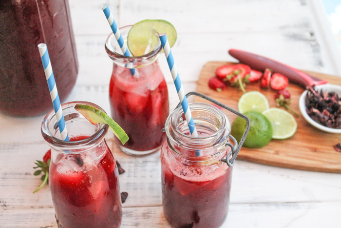 three clear glasses of red hibiscus sweet tea with lime and strawberry