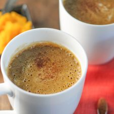 horizontal image of a white mug filled with a orange hued frothy beverage topped with a sprinkle of cinnamon on a fall coloered linen and fresh pumpkin puree in the background on a dark wood surface