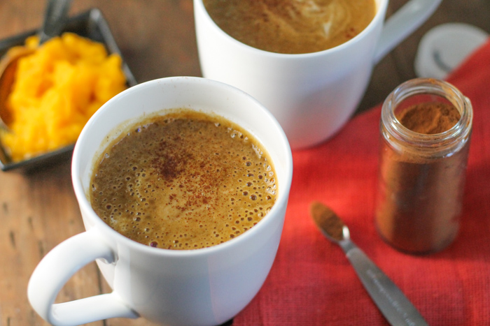 horizontal image of two white mugs filled with an orange hued frothy coffee latte on a dark wood surface with an orange linene cloth and a ramekin of fresh pumpkin puree