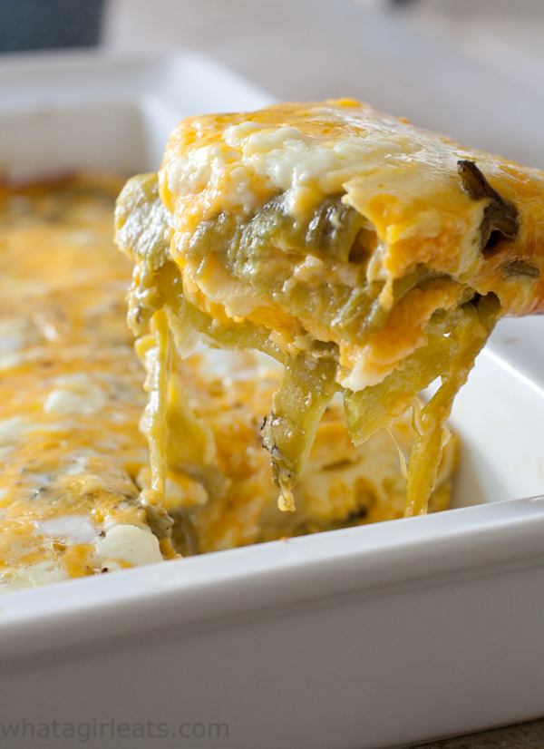 close up melty cheese shot of a layered hatch chili and cheese casserole scoop