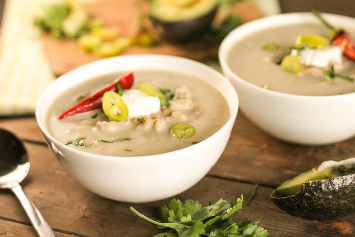 two white bowls with a creamy white chicken chili with sour cream, cilantro, and red chili garnish atop a dark wooden board