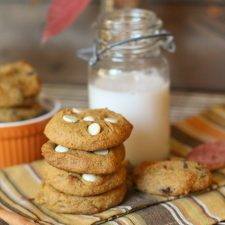 vertical image of 4 stacked pumpkin cookies with a vintage milk jar and fall themed linen
