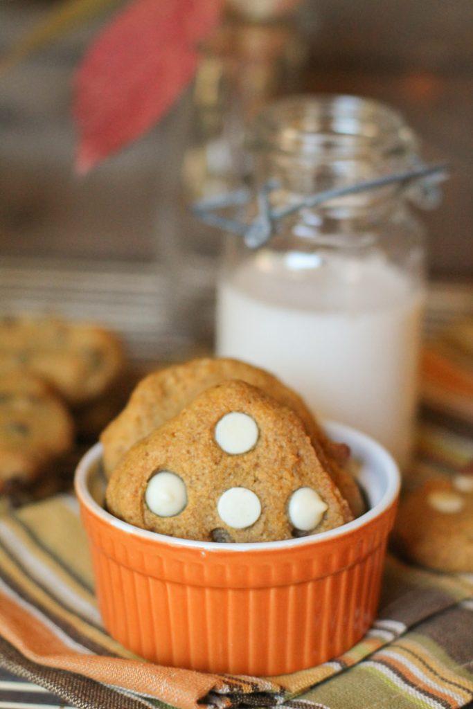 a few white chocolate studded pumpkin cookies standing in pumpkin orange ramekin with a glass of milk in background
