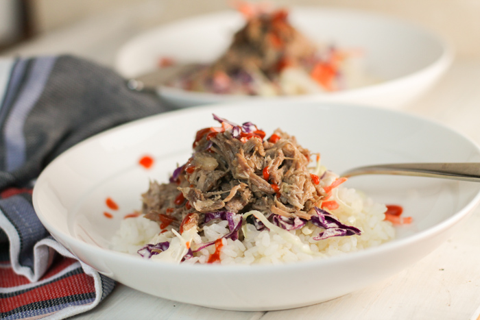 two white pasta bowls filled with sticky white rice, fresh coleslaw, and tender pulled kalua pork with garnish of Siracha