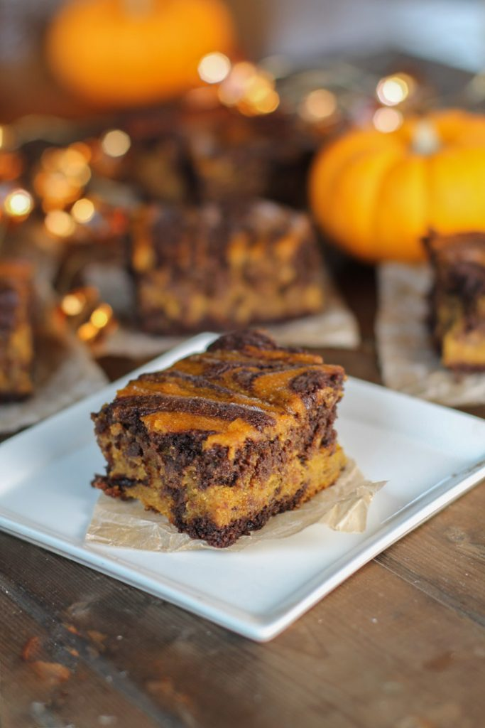 moody low level lighting of a swirled chocolate and pumpkin brownie on a white square plate with glowing amber lights