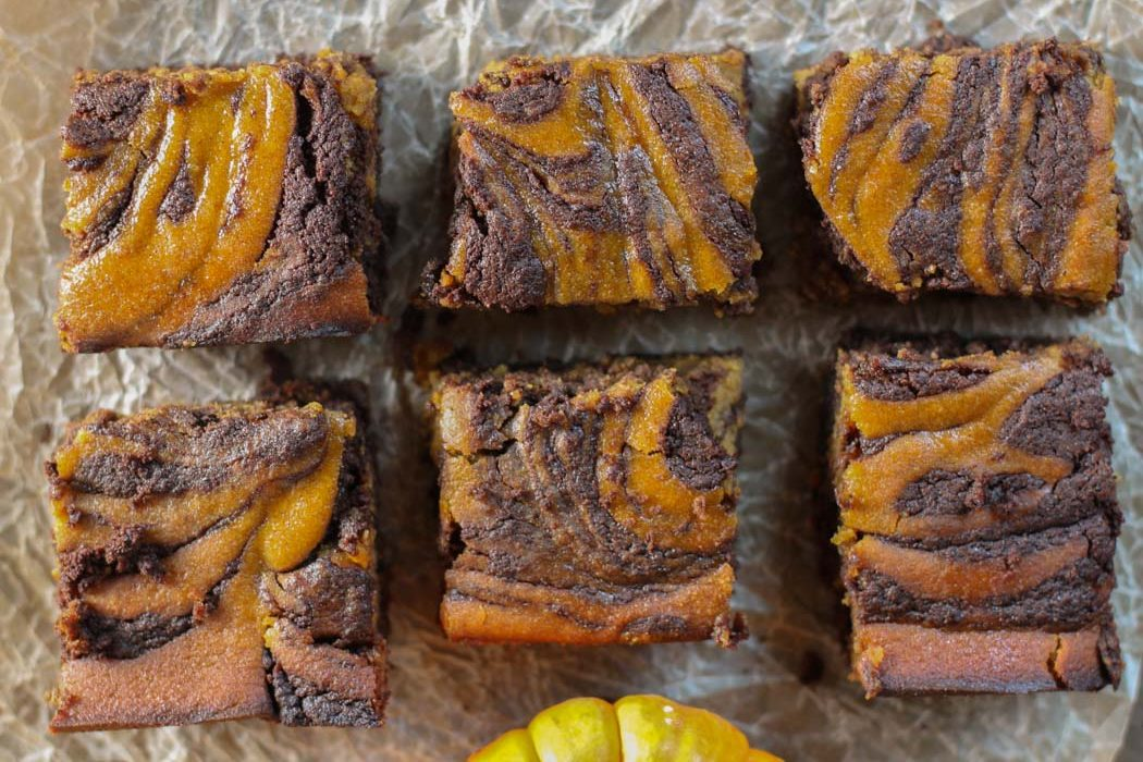 horizontal image of pumpkin and chocolate swirled brownies in two rows with a crumbled natural piece of parchment underneath