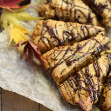 horizontal image of chocoalte drizzled pumpkin scones from overhead atop a crumpled parchment paper and fall leaves scattered about