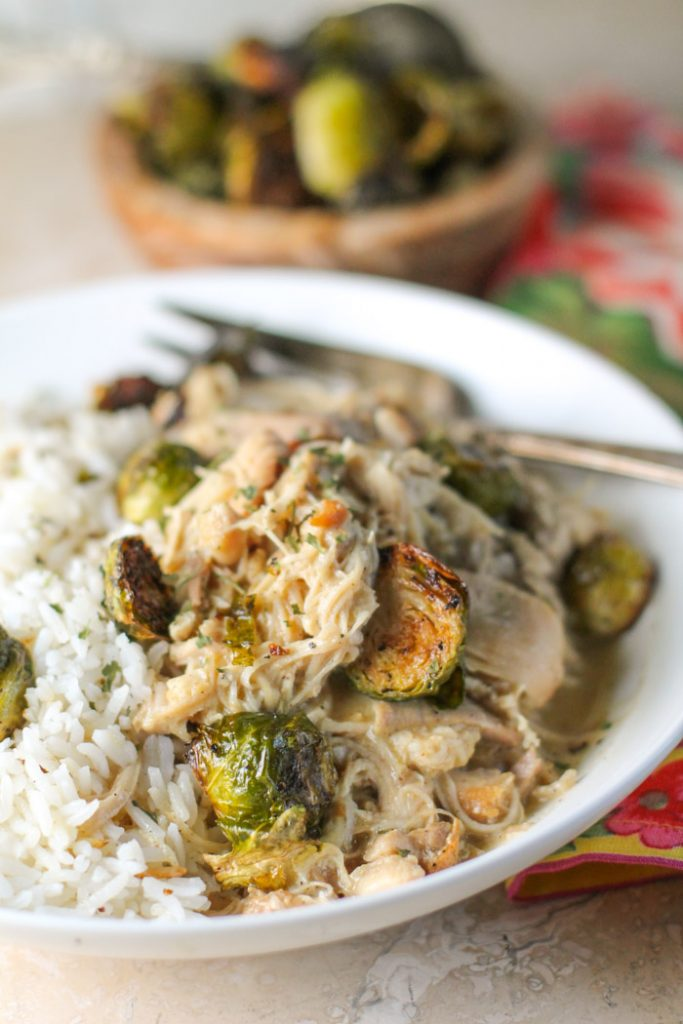 a white pasta bowl on tender shredded chicken and roasted brussel sprouts in a white bowl with a tarnished silver fork