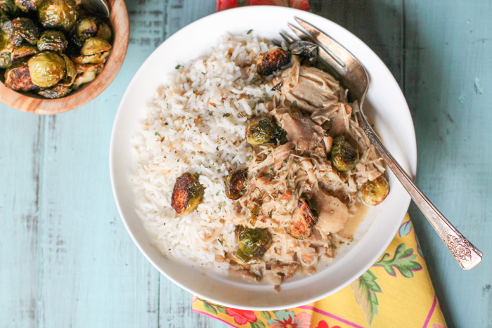 horizontal image of an overhead shot of a white filled with white rice, roasted Brussel sprouts with a slight charring, and tender pulled chicken on an aqua wooden surface