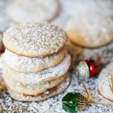horizontal image of 5 stacked cheesecake cookies sprinkled with powdered auagr on a cookie sheet with a garlnad of red and green ornaments scattered about