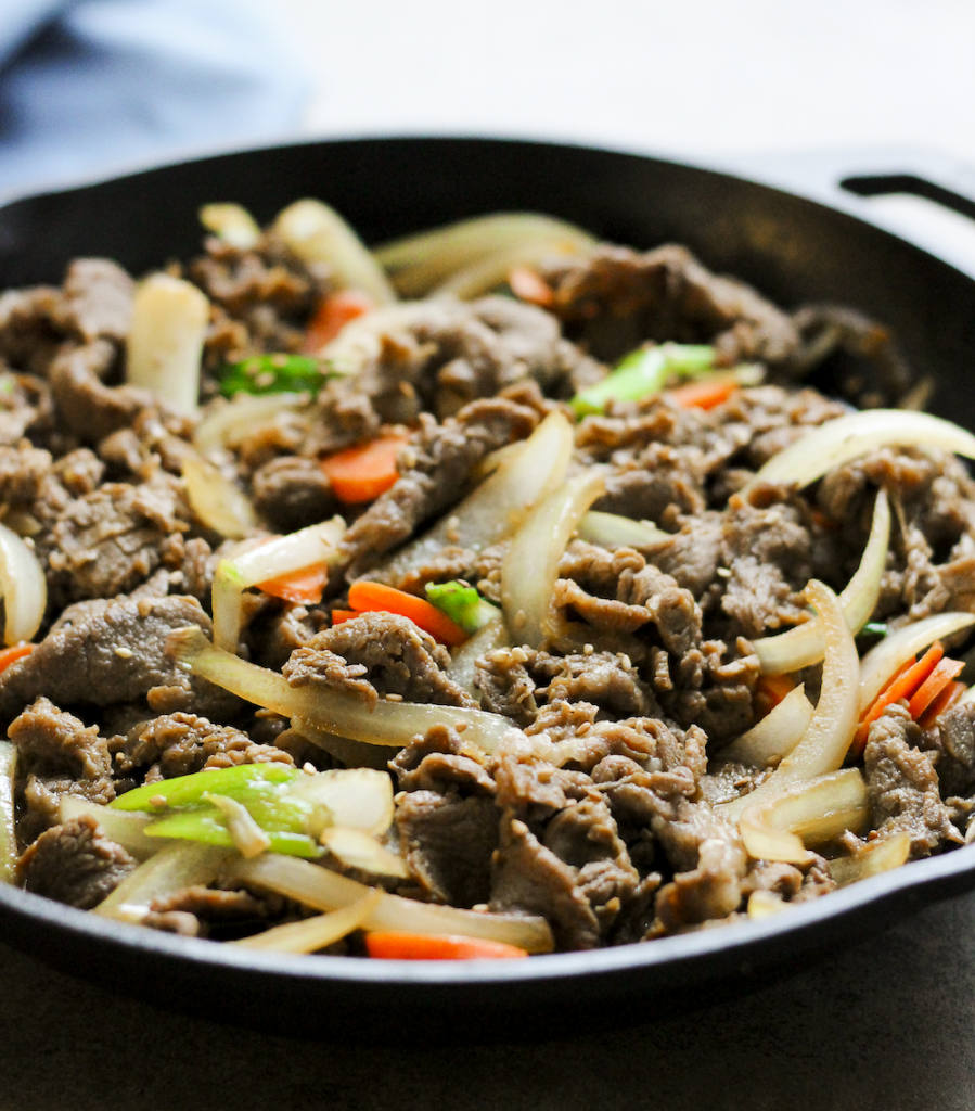eye level shot of a cast iron pan filled with thinly sliced and cooked beef, onions, and peppers