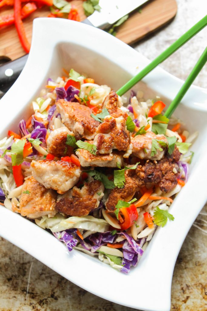 vertical image of a sqaure white bowl filled with cabbaje slaw, fresh red pper, and crispy sesame coated chicken bites with green chopsticks atop a worn steel cookie sheet