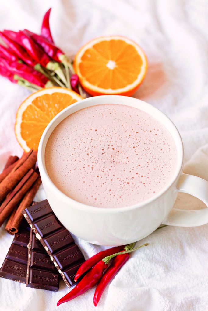 a birds eye view of a froth mug of hot chcoclate ona light surface surrounded by orange slices, cinnamon sticks, chocolate bars, and red chiles