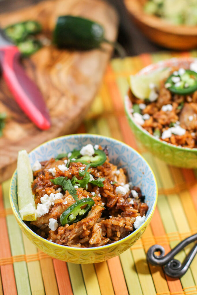 two bowls filled with arroz con pollo and topped with lime, cilantro, and jalapenos