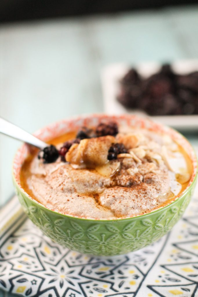 a lime green bowl filled with a creamy nut and seed porridge topped with sliced almonds, berries, and butter