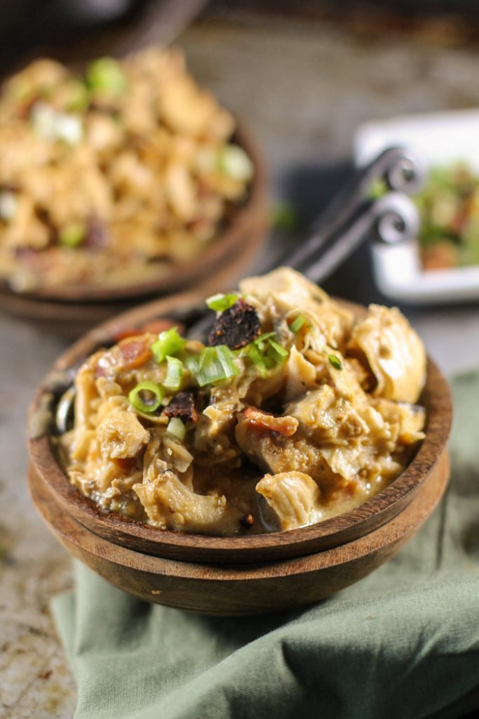 stacked wooden bowls filled with pulled chicken thighs in a creamy sauce with bacon