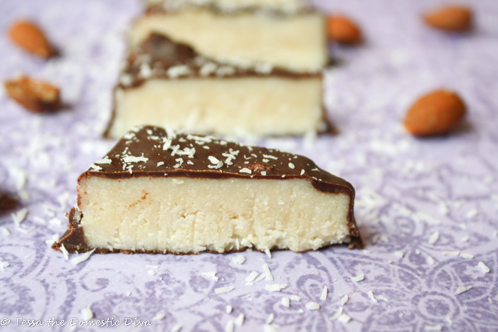 triangle cut chocolate coated coconut bars with raw almonds on a purple cloth