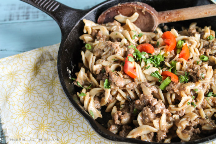 beef, noodles, cheese, cooked up in skillet with a wooden serving spoon