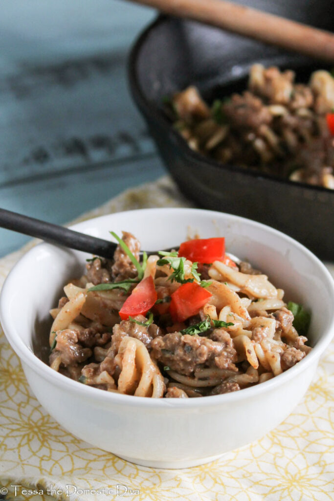 a white filled with noodles, ground beef in a savory cheesy sauce with a red pepper garnish