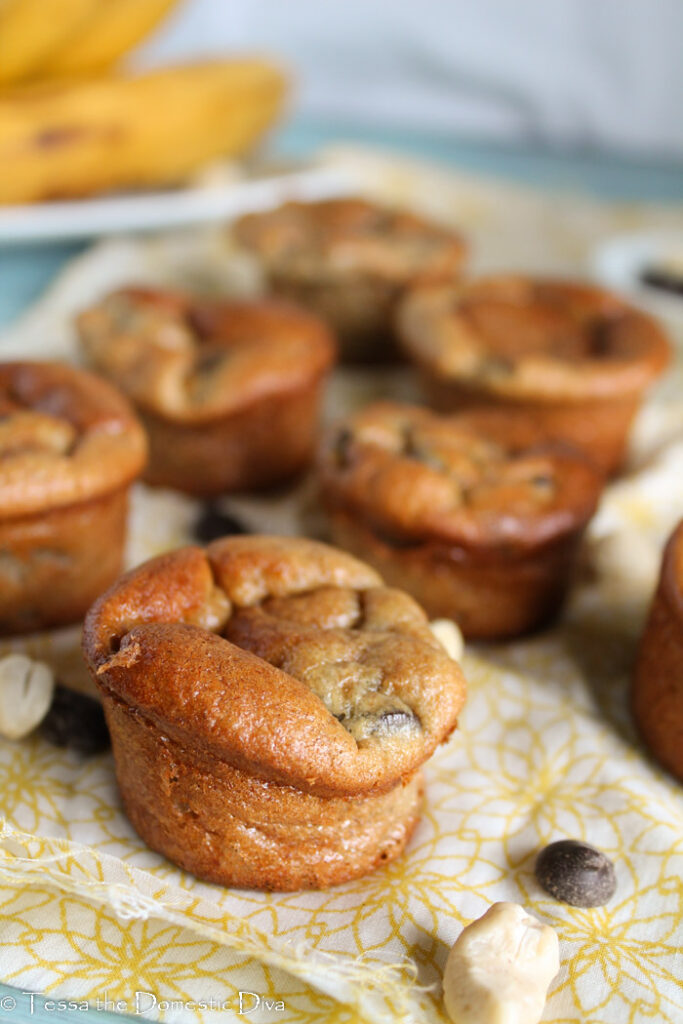 several chocolate chip studded mini muffins arranged on a pale yellow cloth with a raw cashew and a rip banana in background