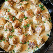 an overhead view of a cast iron skillet filled with golden turkey meatballs coated in a creamy sauce