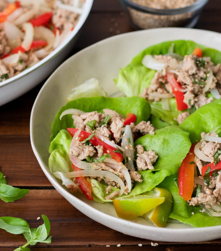 frontal view of two white bowls atop a dark wooden surface filled with butter lettuce leaves topped with ground turkey and red bell peppers and fresh basil