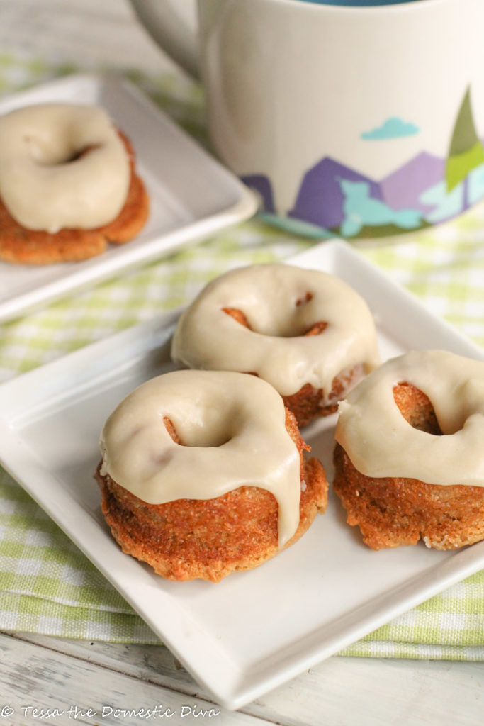 three vanilla cake donuts drizzled with vanilla glaze atop a square white plate with coffee mug in background