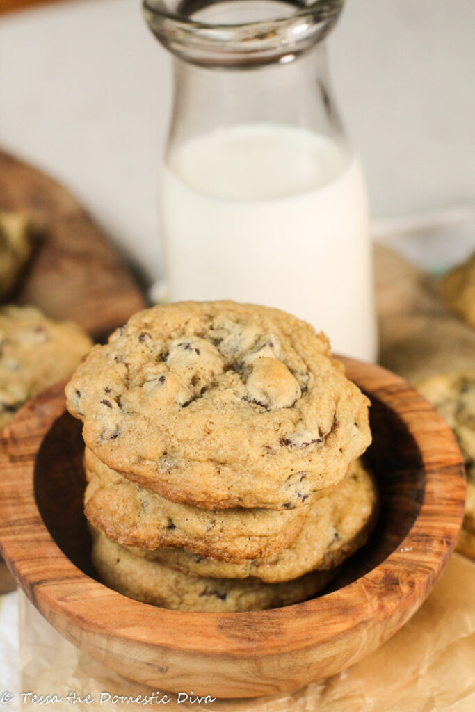 5 chocolate chip cookies stacked in an olive wood bowl with a vintage milk glass