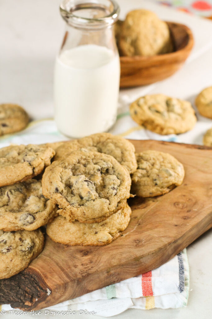 chewy chocolate chip cookies arranged on an olive wood board with a vintage milk glass on a white surface