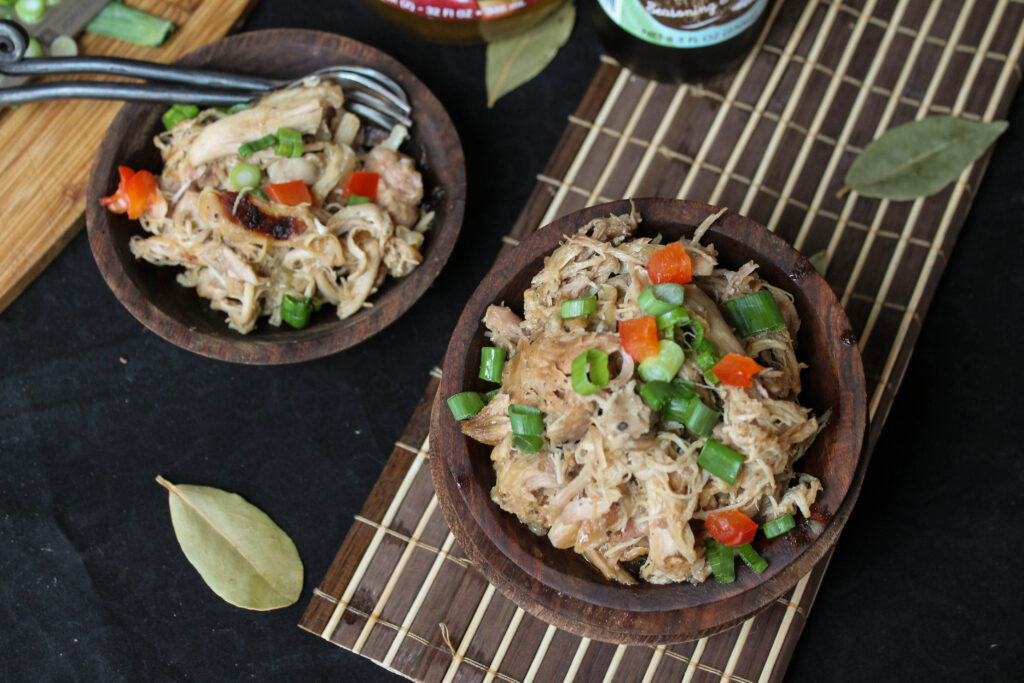 birds eye view of two wooden bowls filled with tender shredded chicken adobo with green onions and red pepper garnish