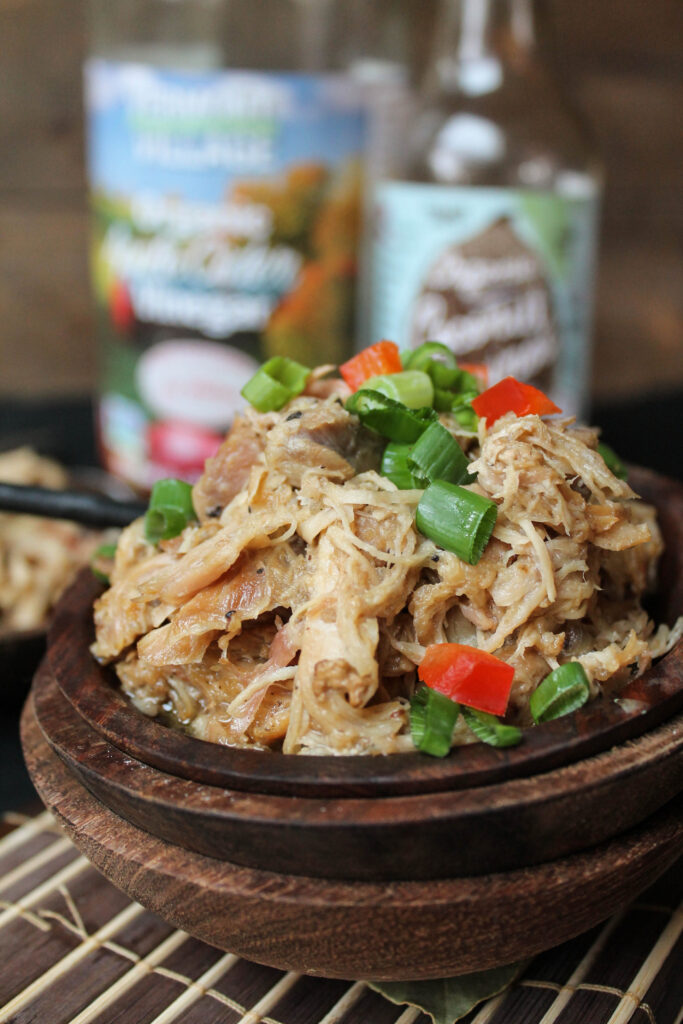 close up front view of several stacked wooden bowls with tender shredded chicken thighs with scallions and red peppers