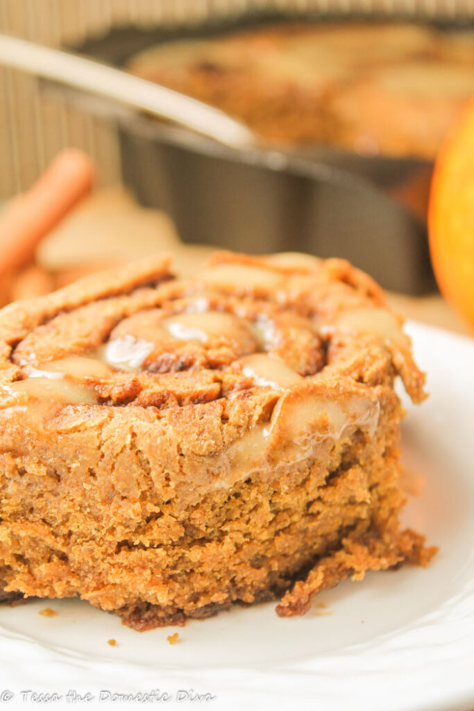 a single pumpkin cinnamon roll on a white plate with a pan in the background