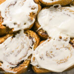 overhead shot of a glass rectangle baking pan fill with cream cheese frosted pumpkin cinnamon rolls