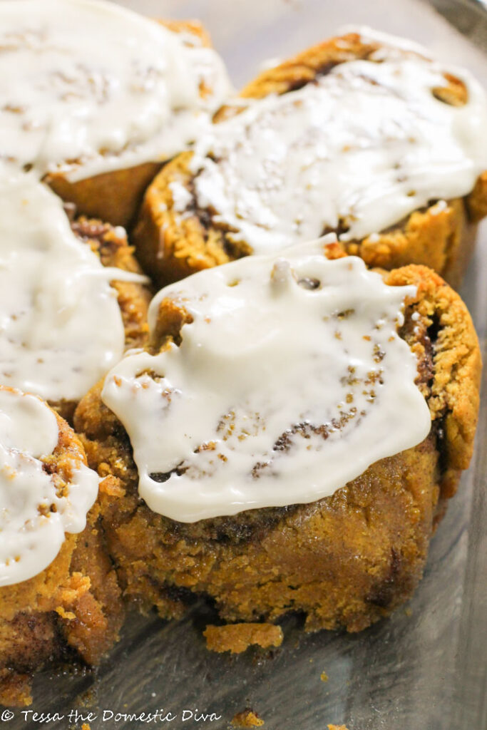 cream cheese glazed pumpkincinnamon rolls in a glass baking pan