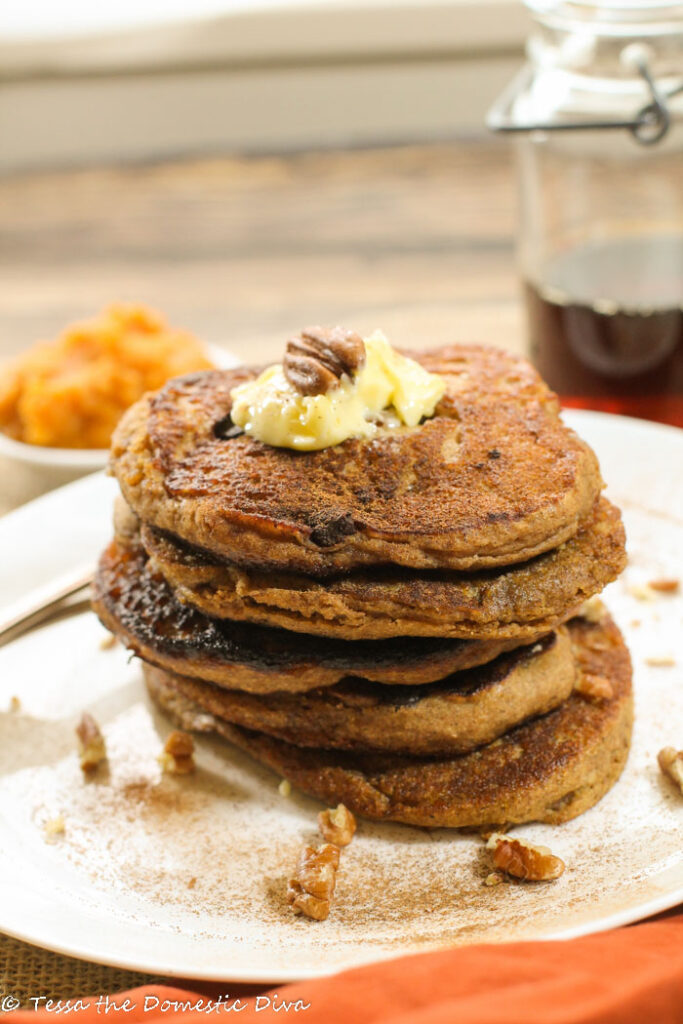 a stack of pumpkin pancakes on a white pate with a dusting of cinnamon and a topped with butter and a whole pecan