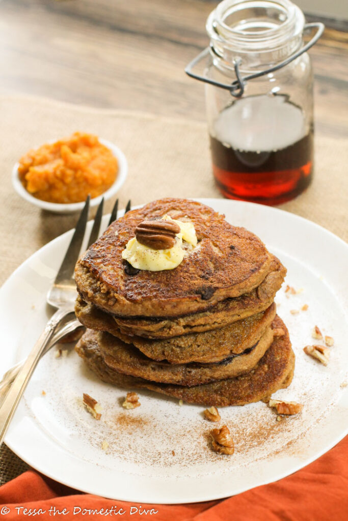a white plate with a stack of pumpkin pancakes topped with butter and pecans and a real maple syrup