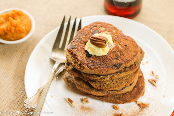 a stack of 6 orange hued pancakes with a pat of butter and a whole pecan with pumpkin puree in background