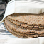 a stack of brown tinted wholegrain fresh tortillas wrapped in a white cloth with a cast iron tortilla press